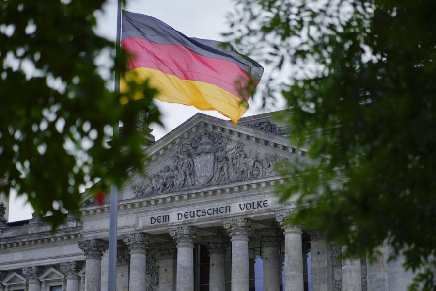 The+German+national+flag+waves+in+front+of+the+German+parliament+building%2C+the+Reichstag+Building%2C+with+the+slogan%3A+To+The+German+People+in+Berlin%2C+Tuesday%2C+Sept.+28%2C+2021.+Germanys+newly+elected+lawmakers+are+holding+their+first+meetings+as+their+parties+digest+the+fallout+of+the+election+that+reduced+outgoing+Chancellor+Angela+Merkels+bloc+to+its+worst-ever+result+and+start+the+process+of+putting+together+a+new+government.+%28AP+Photo%2FMarkus+Schreiber%29